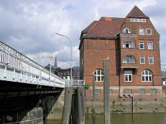 Ericusbrücke, Holzdalben am Ericusgraben in der Hafencity Hamburgs / historisches Verwaltungsgebäude, Hafengebäude.