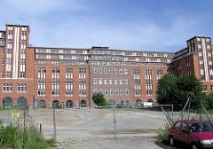 Gebäude vom Bahnpostamt Hühnerposten in Hamburg Hammerbrook - Brachfläche mit Bauzaun.