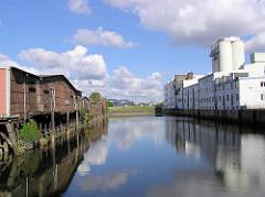 Links denkmalgeschütze Lagerhäuser am Neuhäuser Damm / Marktkanal in Hamburg Veddel, re. Siloanlagen. ( 2004 )