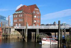 Zollgebäude an der Ericusbrücke / Ericusgraben in der Hamburger Hafencity; eine Barkasse fährt auf dem Fleet Richtung Brooktorhafen.