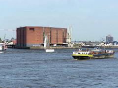 Blick über die Elbe im Hamburger Hafen zur Einfahrt in den Sandtorhafen und das Lagergebäude Kaispeicher A. Re. die Einfahrt zum Grasbrookhafen und das Hotelhochhaus in Rothenburgsort.