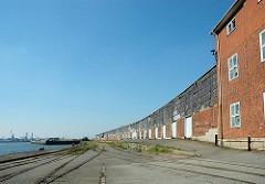 Lagergebäude am Versmannkai / Baakenhafen, Hafenbecken im Hamburger Hafen. Schienen der Hafenbahn auf dem Kai.