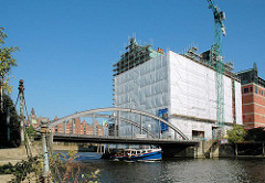 Bauarbeiten am Kaispeicher B - Umbau zum Maritimen Museum - eine Barkasse fährt durch das Hafenbecken Richtung Elbe.