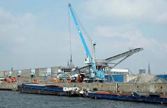 Ein Kran mit Greifer löscht die Ladung eines Binnenschiffs am Kirchenpauerkai im Hamburger Hafen.