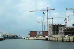 Blick über den Grasbrookhafen zu den Baustellen am Dalmannkai und dem Gebäude vom Kaispeicher A im Hamburger Stadtteil Hafencity; ein Container Feeder verläßt den Hamburger Hafen. (2006)