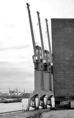 Kräne an der Fassade vom Kaispeicher A / Kaiserspeicher an der Norderelbe in der Hafencity Hamburg - Schwarz-Weiss-Aufnahme. ( 2006 )