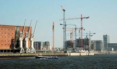 Blick über die Norderelbe zum Grasbrookhafen - Baustellen für Neubauten, Baukräne am Dalmannkai; lks. die Kräne vor dem Kaispeicher A, der zukünftigen Elbphilharmonie Hamburgs.