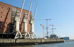 Hafenkräne am Kaispeicher A in der Hafencity Hamburgs - im Hintergrund Baukräne am Dalmannkai im Grasbrookhafen. ( 2006 )