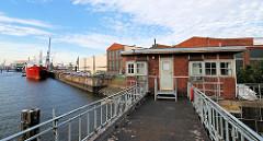Wärterhäuschen / Betriebshaus des Schleusenmeisters, Schleusenwärter der Grevenhofer Schleuse - Blick auf den Kuhwärder Hafen, ein Frachtschiff liegt am Steinwärder Ufer.