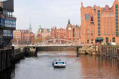 Motive aus dem Hamburger Hafen / Hafencity; Kaispeicher B / Magdeburger Brücke im Magdeburger Hafen, Stahlsäulen im Wasser - im Hintergrund Gebäude der Speicherstadt am Brooktorkai, St. Annen. ( 2006 )
