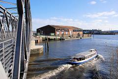 Eine Barkasse kommt aus dem Magdeburger Hafen und fährt Richtung Norderelbe - lks. ein Lagergebäude am Versmannkai / Bueno Aires Kai und die Einfahrt zum Baakenhafen.
