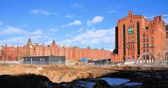 Baustelle am Überseequartier bei der Dalmannstraße in der Hamburger Hafencity; Blick zur Magdeburger Brücke und dem Kaispeicher B am Magdeburger Hafen - im Hintergrund  die Lagerhäuser der Speicherstadt.
