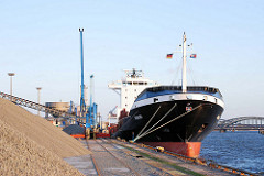 Frachtschiff im Hamburger Hafen - Schüttgut am Kirchenpauerkai; im Hintergrund die Norderelbbrücken.