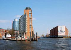 Einfahrt in den Hamburger Sandtorhafen - lks. Bürogebäude am Kehrwieder, re. der Lagerhaus / Kaispeicher A am Kaiserhöft. Werbetransparent mit Bild - Elbphilharmonie Hamburg.