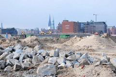 Blick vom Versmannkai im Hamburger Baakenhafen über Geröll und Sandhaufen Richtung Magdeburger Hafen / Speicherstadt.