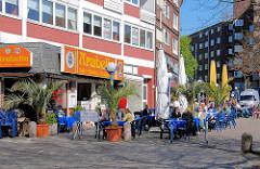Restaurant mit Tischen auf dem Winterhuder Marktplatz; im Hintergrund die Alsterdorfer Straße in Hamburg Winterhude.