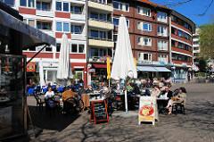 Eiscafé auf dem Winterhuder Marktplatz - Tische mit Gästen in der Sonne; Fotos aus dem Hamburger Stadtteil Winterhude.