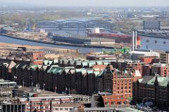 Blick über die Gebäude in der Hamburger Speicherstadt zur Norderelbe und den Norderelbbrücken. Ein Frachtschiff liegt am Kirchenpauerkai - davor das Hafenbecken vom Baakenhafen.