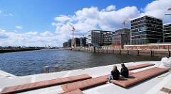 Sitzbänke an der Marco Polo Terrasse mit Blick über den Grasbrookhafen zur Hamburger Norderelbe - re. Neubauten, Neubauwohnungen am Dalmannkai / Vasco da Gama Platz.