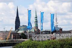Flaggen der Hafencity am Strandhöft - im Hintergrund die Baakenbrücke über den Magedburger Hafen und die Kirchtürme der St. Nikolaikirche und der St. Katharinenkirche; re. der Hamburger Fernsehturm. ( 2007 )