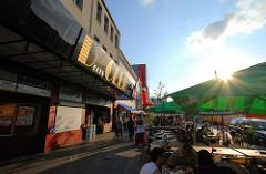 Aussengastronomie am Spielbudenplatz - Tische mit Sonnenschirmen auf dem Fussweg / Docks Club