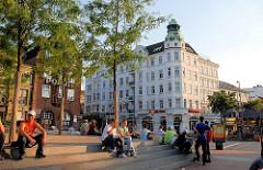 Umgebauter Spielbudenplatz - Sitzplätze auf Treppen in der Sonne - im Hintergrund die Polizeiwache und Gründerzeitarchitetkur an der Davidstrasse.