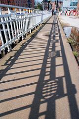 Schatten vom Brückengeländer der Ericusbrücke über den Ericusgraben in der Hamburger Hafencity - Jugendstildekor.