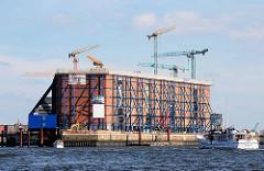 Baustelle der Hamburger Elbphilharmonie - der Kaispeicher ist eingerüstet. Sportboot und Ausflugsboot mit Touristen auf der Norderelbe.