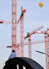 Kräne auf der Baustelle in der Hafencity - ein Parkour Läufer ruht sich auf der Brücke aus - Ballon im blauen Himmel.
