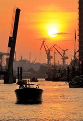 Sonnenuntergang im Hamburger Hafen - die Klappbrücke über den Sandtorhafen ist geöffnet, ein Sportboot fährt in den Traditionsschiffhafen ein - im Hintergrund Hafenkräne im roten Abendhimmel.