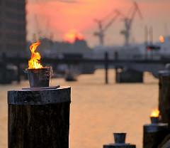 Feuerdekoration auf Holzdalben im Sandtorhafen - Eröffnung des Hamburger Traditionsschiffhafen im Sandtorhafen - Hafenkräne im Hintergrund, untergehende Sonne, roter Abendhimmel. (2008)