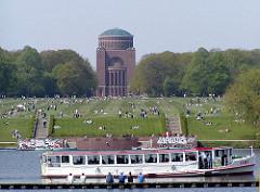 Blick über den See im Stadtpark in Hamburg Winterhude zur Grossen Wiese und dem Hamburger Planetarium; ein Alsterdampfer fährt auf dem See.
