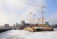 Baustelle vom Spiegelgebäude an der Ericusspitze in der Hamburger Hafencity - Baukräne am Bauplatz; lks. der Ericusgraben - re. der Zollkanal.