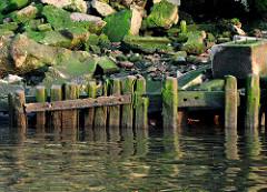 Alte verfallene  Kaimauer im Hamburger Hafen; der Holzsockel ist verwittert und nur noch rudimentär vorhanden. Verblendsteine und Ziegel liegen als Schutthaufen am Elbufer.