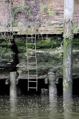 Ebbe im Hamburger Hafen - der untere Teil einer alten Kaimauer ist freigelegt - die Kaianlage ist auf Holzstämmen gegründet. Eine verbogene Eisenleiter führt zum Wasser, in der Ziegelsteinverblendung wächst Wildkraut.