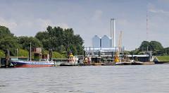 Arbeitsschiffe am Anleger Entenwerder, Hamburg Rothenburgsort / Norderelbe; am Ponton haben ein Binnenschiff und mehrere Schlepper festgemacht - ein Schwimmkran liegt zwischen mehreren Schuten. Dahinter die Tore vom Sperrwerk Billwerder Bucht u