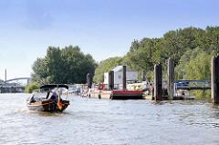 Ein historisches Tuckerboot kommt aus der Billwerder Bucht und passiert den Anleger in Entenwerder, Hamburg Rothenburgsort. Im Hintergrund die Norderelbbrücken.