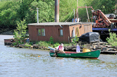 Alter Liegeplatz in der Billwerder Bucht in Hamburg Rothenburgsort; ein Hausboot liegt auf einem mit jungen Bäumen und Wildkraut bewachsenen Ponton. Ein Hafenfischer zieht seine Reuse ins Boot. (2012)