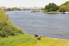 Blick über die Einfahrt zur Billwerder Bucht zu den Norderelbbrücken - Angler sitzen am Wasser, ein Sportboot in Fahrt Richtung Sperrwerk. Rechts die Halbinsel Entenwerder, Arbeitsboote liegen an Pontons und Wasserbrücken.