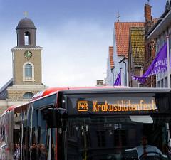 Autobus mit Fahrtziel Krokusblütenfest - im Hintergrund der Kirchturm der Marienkirche am Husumer Marktplatz.
