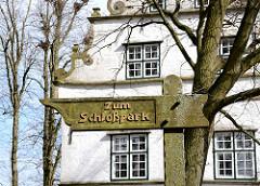 Geschnitztes Holzschild - Hinweisschild Zum Schlossparkt - im Hintergrund die Fassade vom Torhaus.
