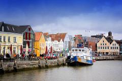 Häuser mit bunter Fassade, farbigem Anstrich am Husumer Binnenhafen - Hafenpromenade mit Aussengastronomie, Tische am Hafenrand.