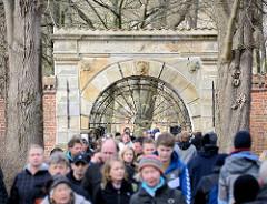 Eingangsportal zu Schlosspark des Husumer Schlosses bei der Krokusblüte - - Menschenmenge, viele Besucher.