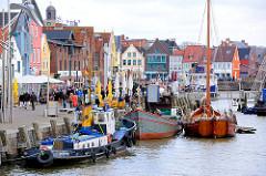 Binnenhafen von Husum - ehem. Werfthafen - Promenade mit Touristen und farbigen Hausfassaden - Schiffe am Kai.