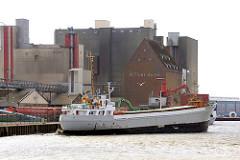 Hafen der Nordseestadt Husum; Industriearchitektur - Lagergebäude, Silos. Das Frachtschiff Hannelore legt vom Hafenkai ab.