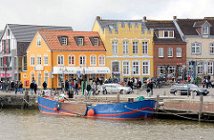 Husumer Binnenhafen - historische Architektur der Nordseestadt - restaurierte Wohnhäuser mit gelber Hausfassade.
