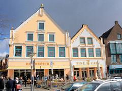 Restaurierte historische Architektur am Binnenhafen Husums - Cafe und Bäckerei mit Tischen in der Sonne.