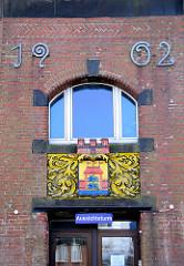 Fassade des Husumer Wasserturms - Jahreszahl 1902, Husumer Stadtwappen. Tor und Palisade, drei Flaggen auf dem Tor.