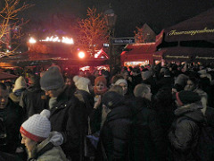 Verkauf / Ausschank von Feuerzangenbowle auf dem Nürnberger Weihnachtsmarkt - der Platz ist mit Bowle trinkenden BesucherInnen dicht gefüllt.