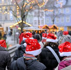BesucherInnen des Weihnachtsmarkts in Erfurt mit roten Weihnachtsmützen / Zipfelmützen bekleidet; beleuchtet Weihnachtsbuden im Hintergrund.